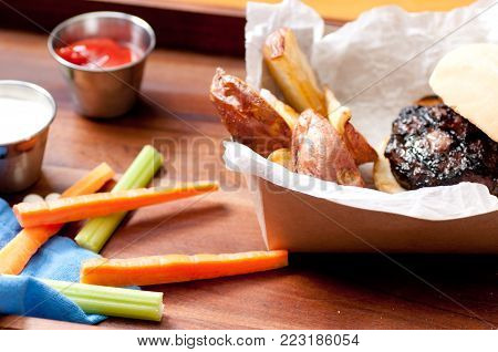 ethically raised pork burger with hand cut red potato wedges and vegetable sticks take out stock photo