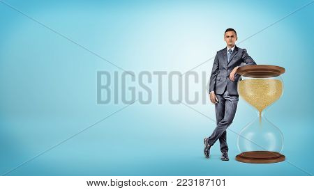 A self-assured businessman leans on a large hourglass with a wooden frame. Keeping in schedule. Multitasking. Master of time.