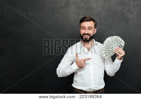 Portrait of adult man in white shirt posing on camera with fan of 100 dollar bills in hand being rich and happy over dark gray background