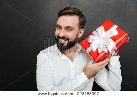 Portrait of curious man shaking red box gift wrapped and trying to recognize what's inside over dark gray wall