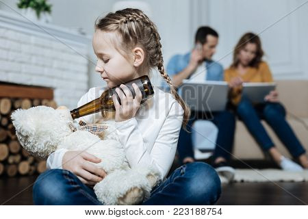 Teddy bear. Sad fair-haired little girl holding a bottle of beer and giving it to her teddy bear while her parents working on their laptops