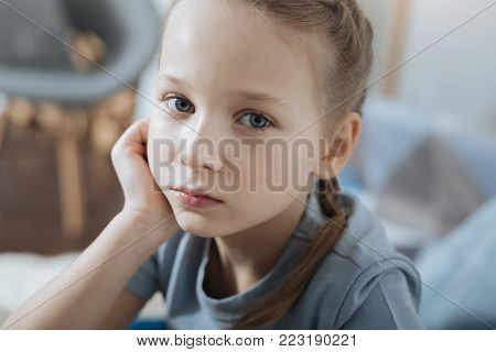 Seriousness. Unsmiling fair-haired blue-eyed little girl thinking and holding her head with her hand while sitting on the sofa