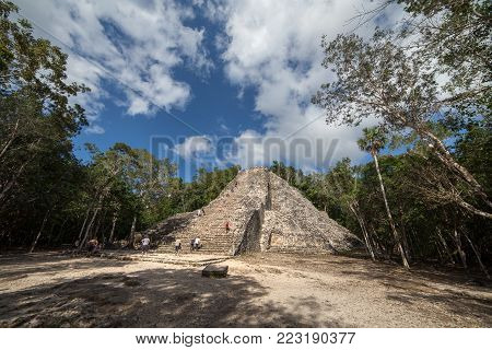 View of ancient Mayan Pyramid in Coba, Mexico. People climbing the stone steps.