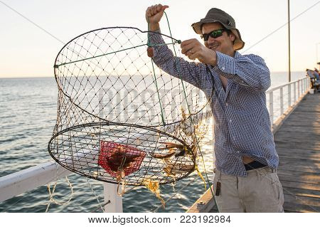 young happy and proud attractive fisherman showing fish and crabs basket net captures smiling at sea dock sunset in man fishing as weekend hobby concept and holidays leisure concept