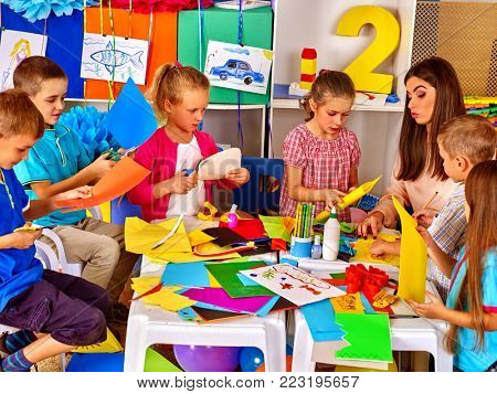 Children and colored paper. Making something on table in primary school. Craft lesson in primary school. Development kids craft at class in school. Children with teacher make overall project.