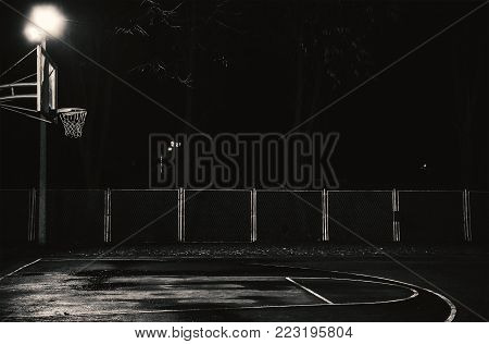Emtpy basketball court by night, details of hoop and terrain.