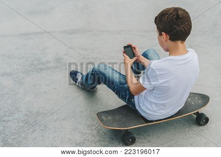 Back view. Teenager, dressed in white t-shirt, sits outdoor on skateboard and uses smartphone, digital gadget, plays computer games, browsing internet, chatting. Social networks, social media.