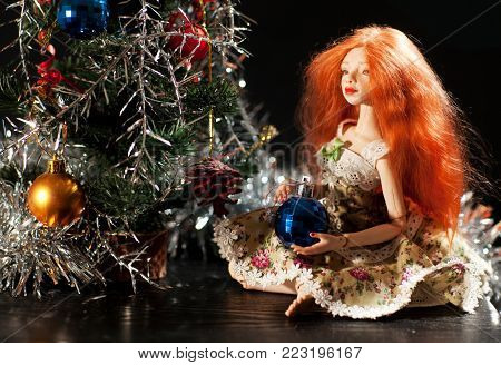 A beautiful doll with a Christmas toy. Red-haired doll on a black background