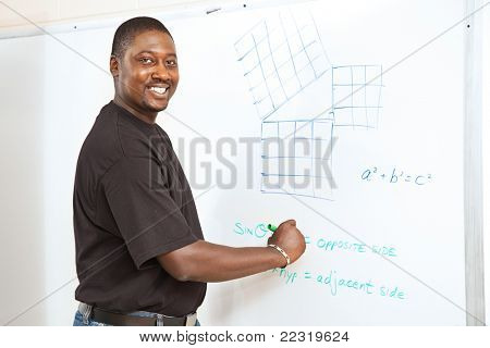 Handsome African-American college student (or teacher) doing trigonometry equations on the white board.