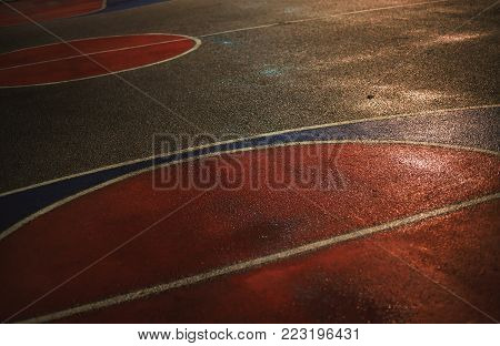 Lines and colors on asphalt of basketball court by night.