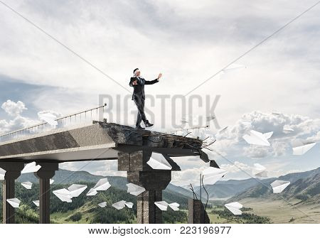 Businessman walking blindfolded among flying paper planes on concrete bridge with huge gap as symbol of hidden threats and risks. Skyscape and nature view on background. 3D rendering. poster