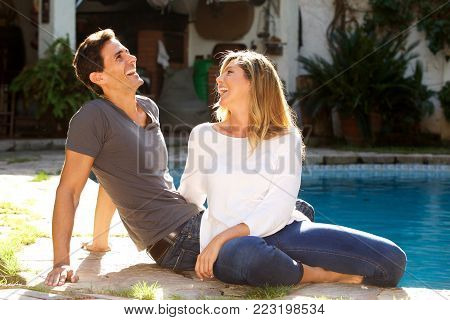 Close Up Happy Couple Sitting Together Outside By Pool