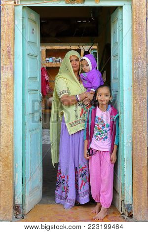 JAISALMER, RAJASTHAN, INDIA - DECEMBER 18, 2017: Portrait of a woman with her two children at the entrance of their house