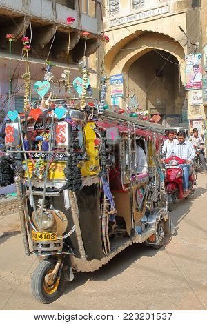 NAWALGARH, RAJASTHAN, INDIA - DECEMBER 28, 2017: A colorful and decorated Tuk Tuk with an entry gate to the Old Town in the background