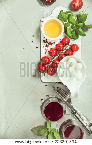 Italian antipasti snack for wine. Mozzarella cheese, fresh basil leaves, tomatoes, olive oil and glasses of red wine on concrete background, top view. Caprese salat ingredients