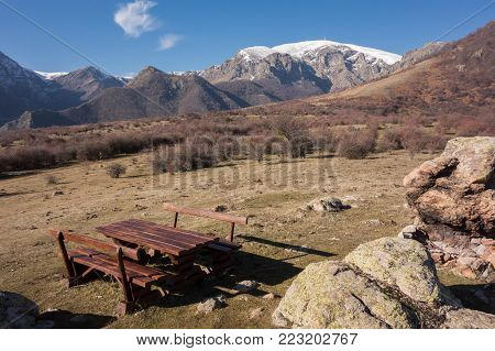 Wooden table and benches for tourist rest zone at the trail to Botev peak. Central balkan national park, Stara planina mountain, Bulgaria
