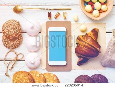 White smart phone on white wood among cookies and sweets. Top view with clipping path.