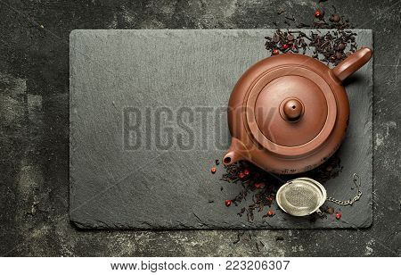 Traditional brown clay teapot on a black stone tray, Chinese black tea with dry berries and small chocolades. Top view with copy space.