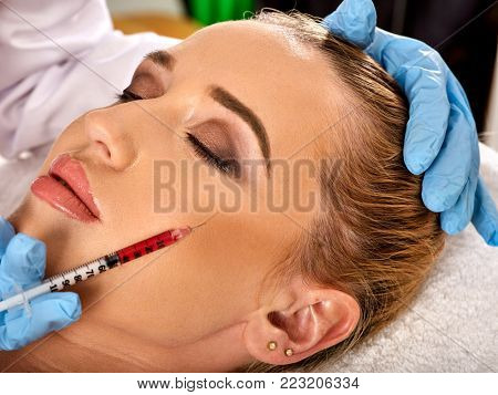 Filler injection for female forehead face. Plastic facial surgery in beauty clinic. Beauty woman giving injections. Doctor in medical gloves with syringe injects cheeks drug. poster
