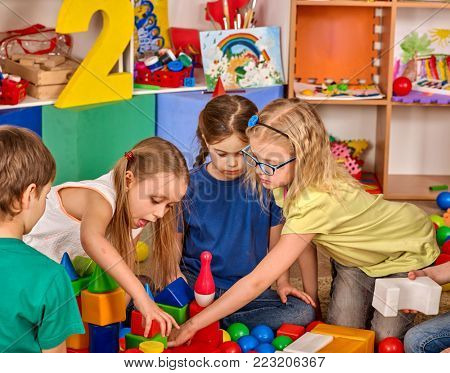 Children building blocks in kindergarten. Group kids playing toy on floor. Top view of interior preschool. Building a tower of cubes. Newcomer learns at new school.
