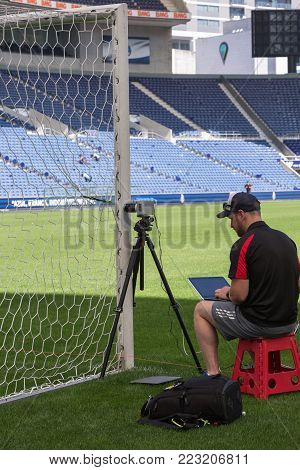 Oporto, Portugal - july 2016: Technician with Laptop Sets up New Goal Line Technologies in Empty Stadium Before Soccer Match