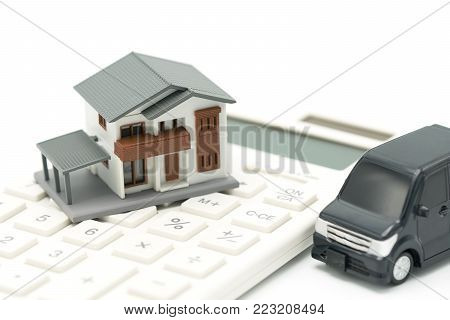 A model house model and car model is placed on a calculator. as background property real estate concept with copy space for your text or  design.