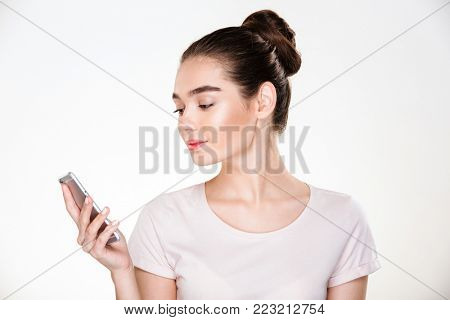 Picture of female with brown hair in bun chatting or reading ebook using smartphone, isolated over white background