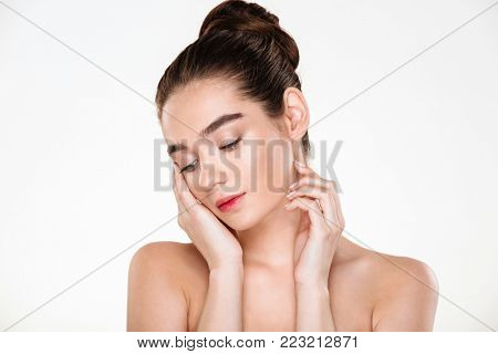 Horizontal portrait of tender woman being half-naked posing over white background with face downward, touching her face