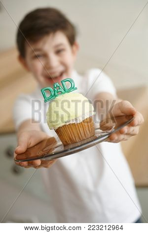 Little boy holding a cupcake made for fathers day.