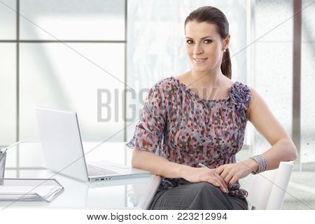 Portrait of attractive office assistant woman sitting at desk with laptop, smiling at camera confidently.