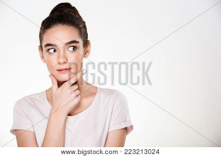 Image of serious woman with brown hair in bun touching her chin while thinking or weighing the pros and cons, posing isolated over white background