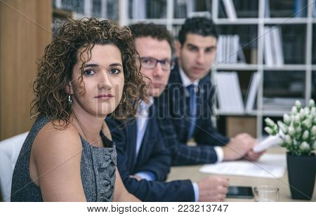 Portrait of female executive chief sitting at the negotiating table with her team in headquarters