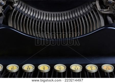 Closeup of an antique typewriter showing a row of keys and the carriage.