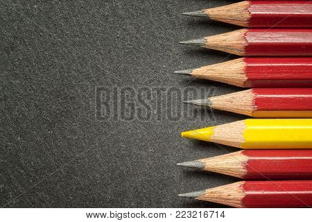 Yellow pencil standing out from crowd of plenty identical black fellows on black  table. Leadership, uniqueness, independence, initiative, strategy, dissent, think different, business success concept.
