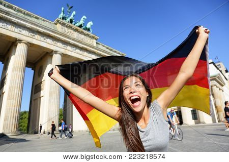 Excited young woman screaming while waving German flag in front of Brandenburg Gate. Cheerful female is enjoying her vacation in Berlin. Beautiful woman is celebrating her holidays.