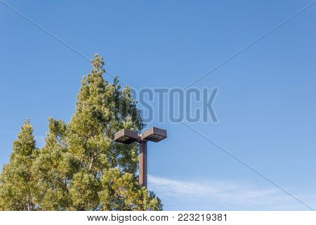 Industrial exterior lighting surrounded by taller trees against a bright blue sky, copy space, horizontal aspect