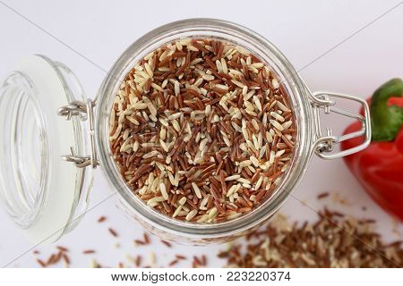 Red (brown) Rice In A Transparent Jar With Lid Yoke, Bulgarian Pepper, White Background