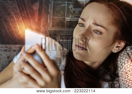 I cant believe in it. Terrified disappointed redhead woman lying on the sofa holding and using her cellphone.