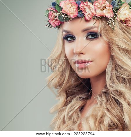 Beautiful Female Face. Nice Young Woman with Makeup, Flowers, Blonde Wavy Hair. Skincare and Haircare Concept
