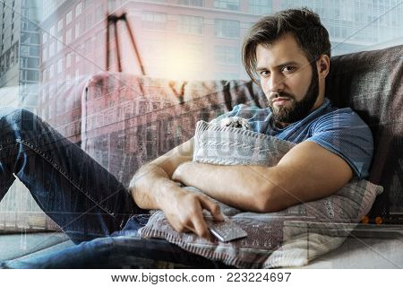 Sadness is coming. Deep exhausted depressed man lying on the sofa hugging the pillow and looking straight.