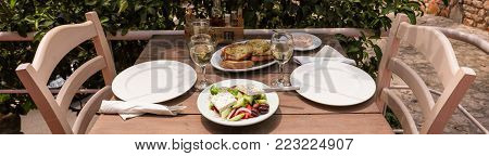 Village greek salad on white plate near glasses of white wine, hot pepper cheese dip dish, plate of bread on wooden table in greek tavern. Horizontal. Close-up. Daylight. View from above.