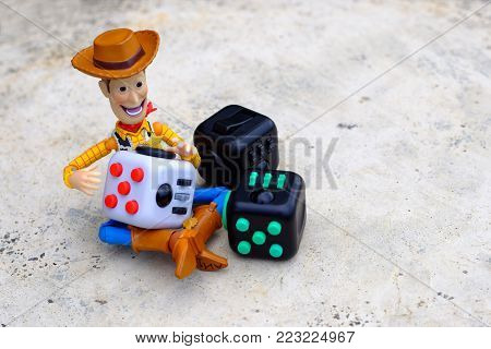 Songkhla, Thailand - January 23, 2018 : Woody playing Fidget Cube stress reliever, Fingers Toy (Relax)