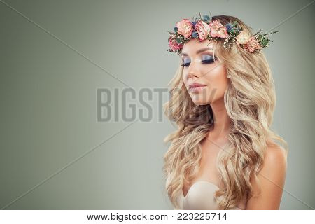 Pretty Blonde Girl with Perfect Makeup, Flowers, Blonde Wavy Hair on Green Background. Skincare and Haircare Concept