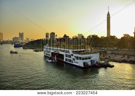 Cairo, Egypt -  Feb 1, 2008: Sunset view on the restaurant in cruise ship on the Nile river moored near promenade. Tourism is one of the most important sectors in Egypt's. More than 12 million tourists visited Egypt annual