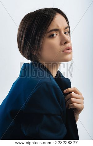 Big problem. Pensive brunette attractive woman posing on the isolated background and looking at the camera while touching lapel