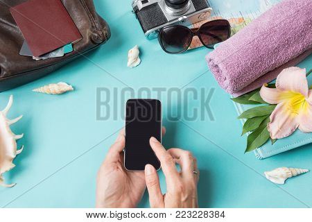 Travel concept, sunglasses and summer accessories on blue background. Smartphone in female hands. View from above. Blank mock up for advertising or packaging.