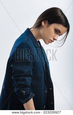 Leave me alone. Wistful budding brunette woman posing in profile  and  escaping from world while lowering head