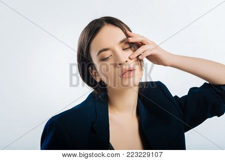 Woman in trouble. Wistful smart gorgeous woman touching her face and dressing in jacket while closing her eyes