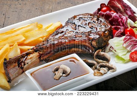 Barbecue Tomahawk Steak with Chips, Salad and Mushrooms