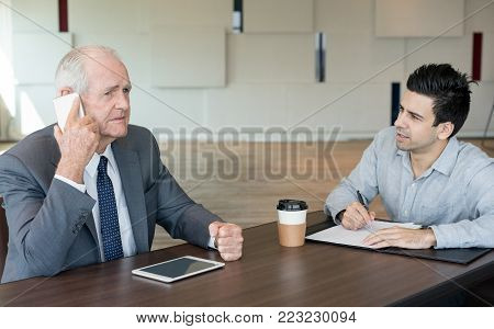 Disappointed senior manager communicating with business partner on phone while knowing bad news. Upset male executive talking on mobile phone while his assistant preparing papers for contract. Failure concept